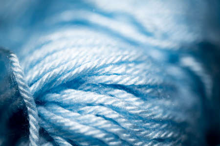 An extreme close-up with selective focus of blue and fuzzy bundled crochet threads.