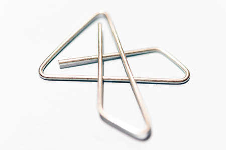 An extreme macro shot with selective focus of an x-style silver metal paper clip set on white background.