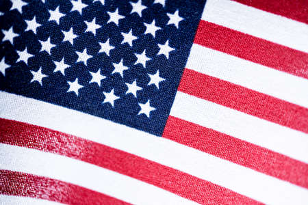A macro shot with selective focus of a small handheld American flag on coarse fabric.