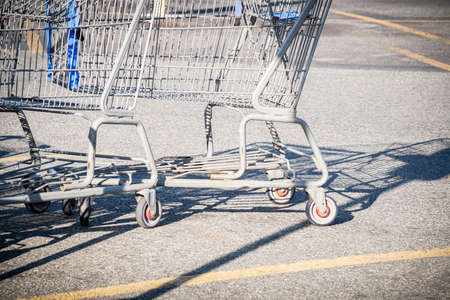 A close-up shot of a shopping cart at the parking lot of a grocery store.