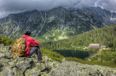 oldschool: Young man with old-school backpack, looking at rocky mountains, cottage and beautiful green lake