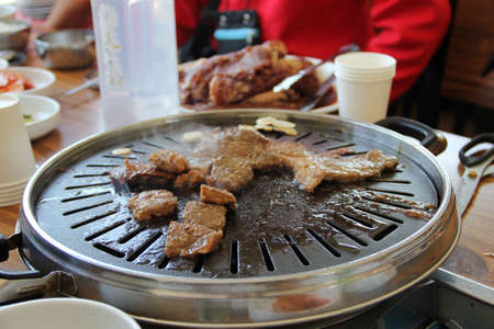 Korean barbecue - meat are being cooked on korean stove Stock Photo