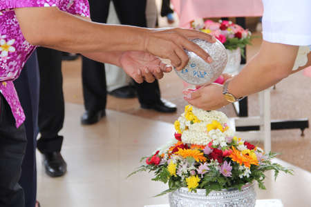 Pour water on the hands of revered elders and ask for blessing Stock Photo - 13699486