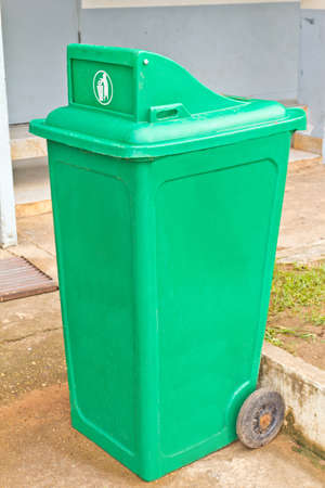 Green garbage bin with wheels photo