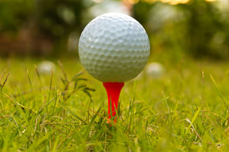 Golf ball on tee over a blurred green. Shallow depth of field. Focus on the ball. photo
