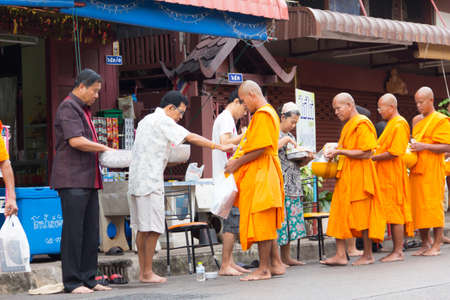 SAKONNAKHON , THAILAND - October 30:unidentified people give food offerings to Buddhist monks on October 30, 2012 in Sakonnakhon, Thailand. Thai traditional, people will make merit making by give food to monk Editorial