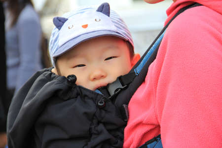 SEOUL,KOREA - APRIL 08 : unidentified  baby in a backpack with my mother  in the knapsack on April 08 ,2011 in Seoul, Korea.