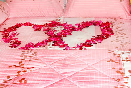Bed covered with a pink towel and a rose petal heart shape Stock Photo - 18020407