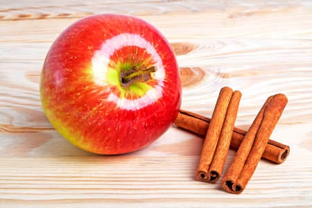 cannelle: Red apple with cinnamon sticks on wooden background
