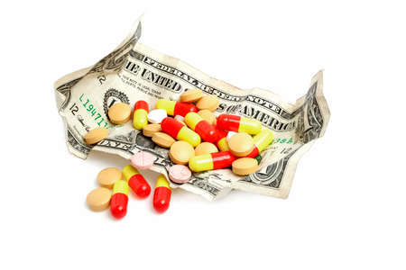 Money with pills isolated on white background
