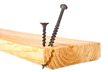Black screws screwed into wooden plank