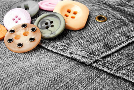 Colored buttons on a black denim Imagens