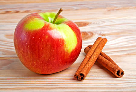 cannelle: Red apple with cinnamon on wooden background