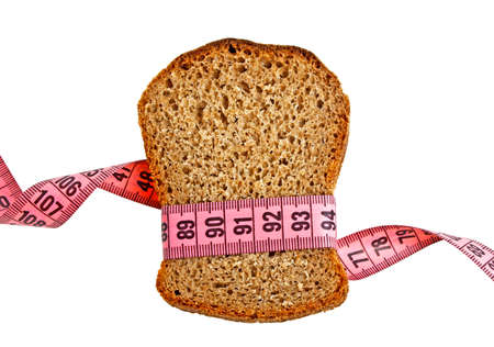 Diet concept - piece of bread grasped by measuring tape isolated on white background