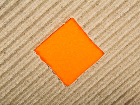Square hole with orange paper in cardboard