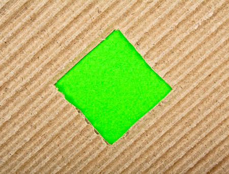 Square hole with green paper in cardboard