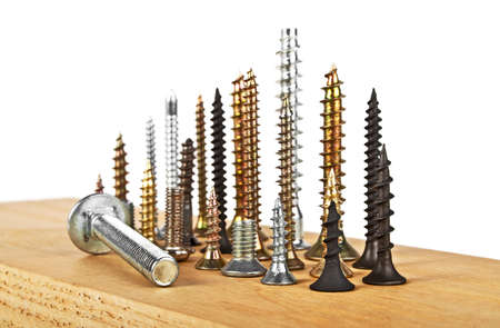 Various screws on wooden plank on a white background Stock Photo