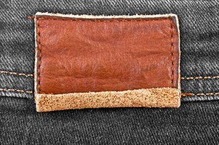 sew tags: Leather jeans label sewed on jeans Stock Photo