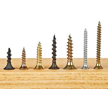 Various screws on wooden plank on a white background Stok Fotoğraf