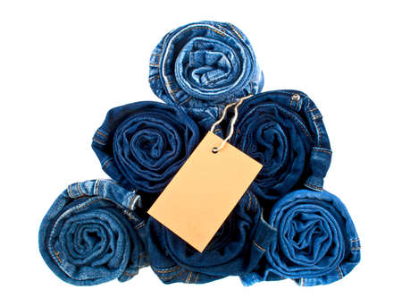 Lot of different blue jeans and brown label on a white background