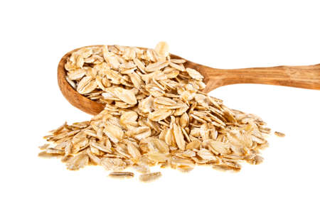 Oatmeal groats in wooden spoon on a white background