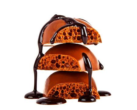 porous: Pieces of tile porous milk chocolate poured chocolate isolated on white background