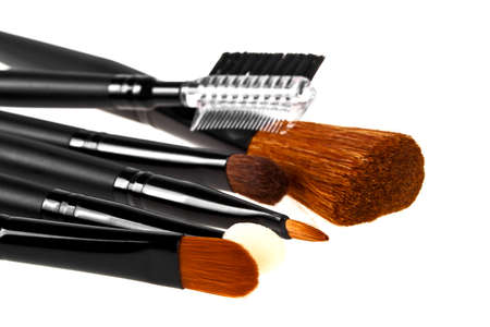grooming product: Bunch of make-up brushes lying randomly on white background