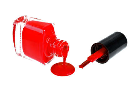 Red nail polish and brush on a white background