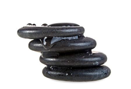 Black massage stones stacked, isolated on white background Stock Photo
