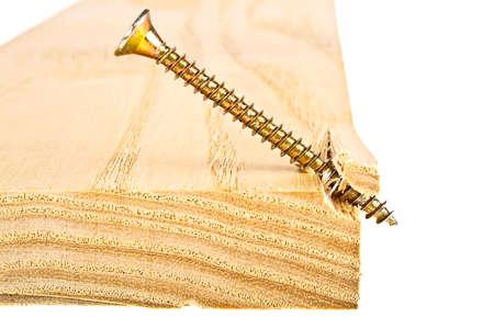 Golden screw screwed into wooden plank