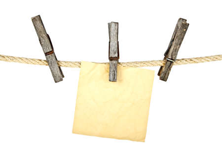 Old wooden clothespins holding brown paper on a white background