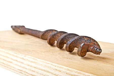 Old rusty drill bit on wooden plank on a white background