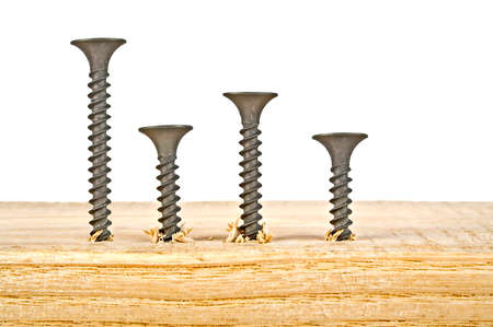 disassemble: Various black screws screwed on wooden plank on a white background