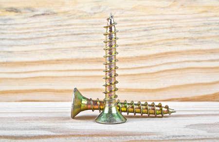 Golden screws screwed on wooden plank Stock Photo