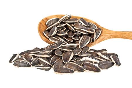 Sunflower seeds on wooden spoon on a white background Stock Photo
