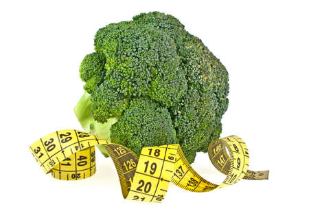 weight control: Fresh broccoli and yellow measuring tape isolated on a white background. Weight control properties of broccoli. Diet concept. Stock Photo