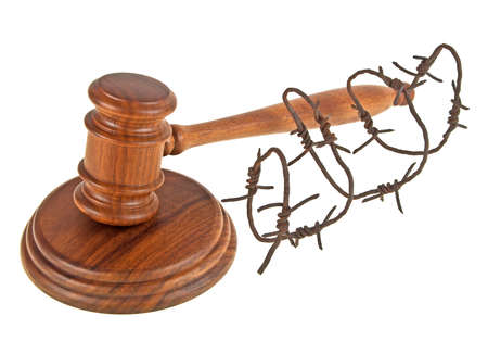 Wooden judge gavel and barbed wire on a white background