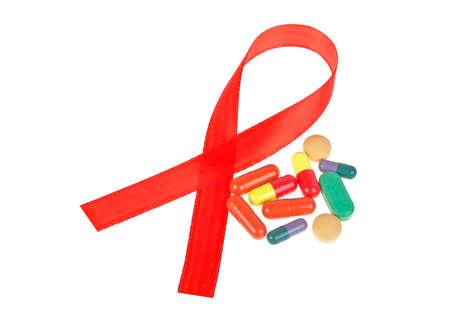 aids awareness ribbon: Red AIDS Awareness Ribbon and Pills. AIDS awareness ribbon on white background. Stock Photo