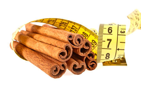 millimeters: Cinnamon sticks wrapped roulette on a white background Stock Photo