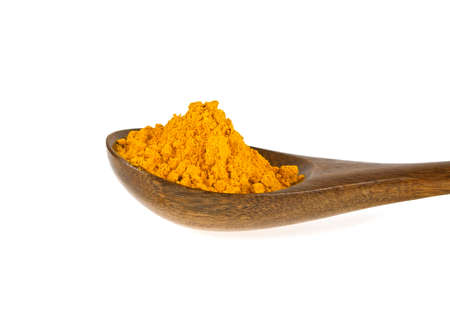 asian flavors: Turmeric powder in wooden spoon on a white background. Curcuma powder. Stock Photo