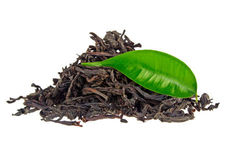 Heap of dry black tea with green tea leaf isolated on a white background Stock Photo