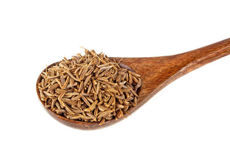 Cumin seeds in wooden spoon, isolated on a white background