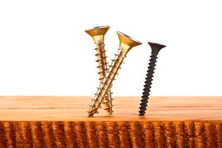 Various screws screwed into wooden plank