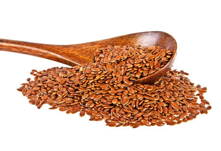 Brown flax seeds. Linseed in wooden spoon closeup isolated on white background.