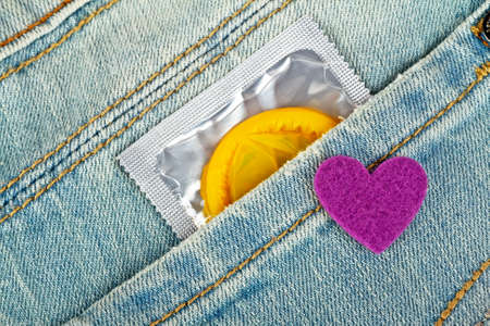 Yellow condom in blue jeans pocket and violet heart