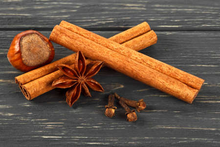 Spices on wooden background. Cinnamon, nuts, anise and cloves. Christmas background.