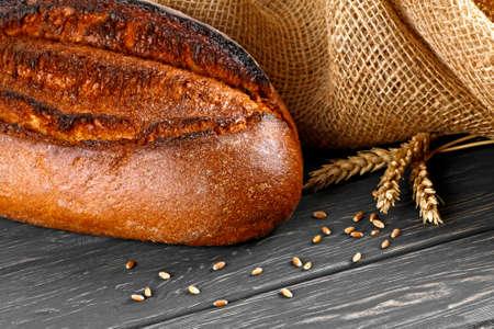 Fresh bread and wheat on wooden table Zdjęcie Seryjne