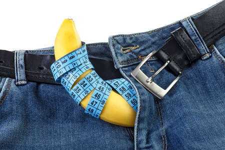 Blue jeans with measuring tape and yellow banana on white background. Mens denim pants with banana imitating male genitals.