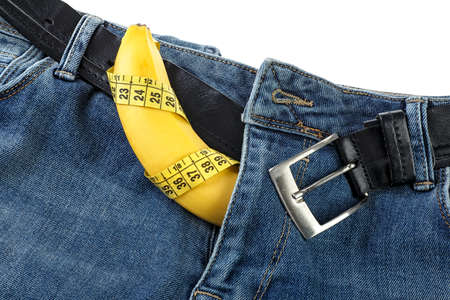 Blue jeans with yellow measuring tape and banana on white background. Mens denim pants with banana imitating male genitals. Standard-Bild