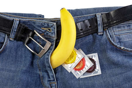 Blue jeans and banana with сondoms, safe sex concept.
